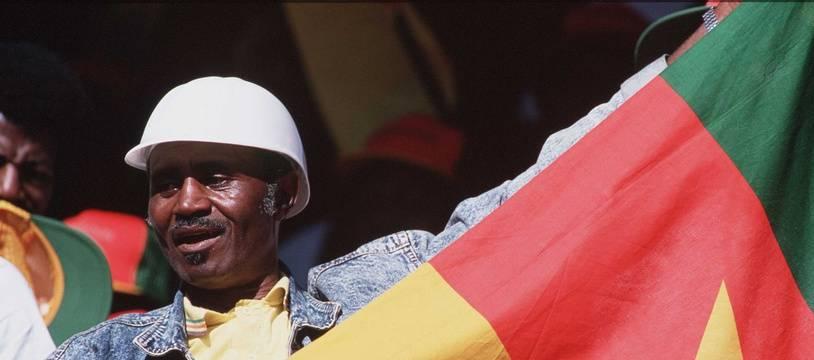 Un homme tient le drapeau du Cameroun dans ses mains