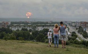 (Illustration) Une famille observe des explosions dans un dépôt de munitions militaires situé près de la ville d'Achinsk, dans la région de Krasnoïarsk, dans l'est de la Sibérie, à Achinsk, en Russie, le 5 août 2019.