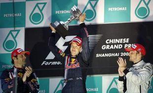 L'Allemand Sebastian Vettel, soulevant le trophée du Grand Prix de Chine, le 19 avril 2009, devant Marc Webber (à gauche ) et Jenson Button.