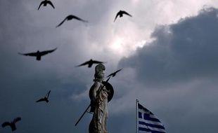 Le drapeau grec flotte devant une statue d'Athéna, dans le centre d'Athènes, le 12 mars 2015