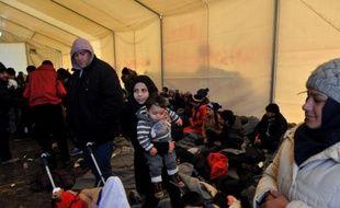 Des migrants et réfugiés, bloqués à Idomeni, à la frontière gréco-macédonienne, se réchauffent sous une tente, le 21 janvier 2016