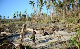 Une femme porte des bananes sur une plage du Vanuatu le 21 mars 2015 après le passage du cyclone Pam.