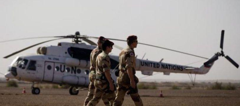 Des soldats français passent devant un hélicoptère de l'ONU stationné sur la base militaire française à Gao, le 31 décembre 2013