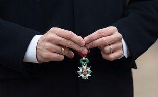 Une légion d'honneur dans les mains d'Emmanuel Macron.