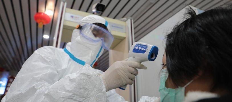 Un homme prend la température d'une habitante à Lanzhou, en Chine
