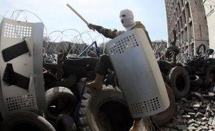 Des militants pro-russe devant une barricade dressée autour de l'immeuble de Service de sécurité régional ukrainien à Donetsk, à l'est de l'Ukraine le 7 avril 2014