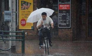 Un cycliste sous une pluie battante dans le quartier commerçant de Ginza à Tokyo le 29 juin 2014