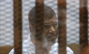 Le président islamiste Mohamed Morsi destitué par l'armée, derrière les grillages du banc des accusés lors de son procès au Caire le 18 août 2014