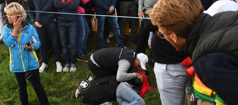 Une spectatrice de la Ryder Cup allongée au sol, touchée au visage par une balle de golf.