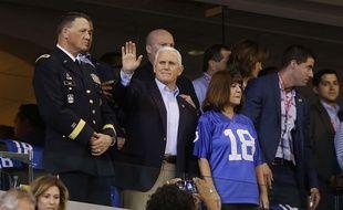Mike Pence salue les supporters lors d'un match de football américain, avant de quitter le stade quelques instants plus tard.