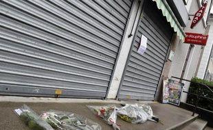 Des fleurs sont déposés devant le tabac où un homme a été tué à Dolomieu le 30 juillet 2014