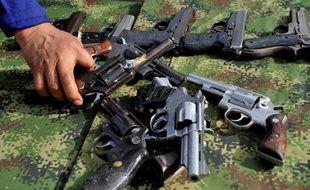 Un soldat colombien saisit une des 9.517 armes saisies aux mains des guérilleros des Farc et de l'ELN avant que celles-ci ne soient fondues pour être recyclées, le 25 novembre 2014 à Sogamoso, en Colombie