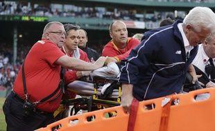 Des soigneurs des Boston Red Sox soignent une femme blessée par un morceau de batte de baseball, à Boston le 6 juin 2015.
