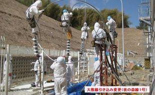 Des employés tentent de rétablir le courant électrique dans les réacteurs 3 et 4 de la centrale nucléaire de Fukushima au Japon, le 18 mars 2011.