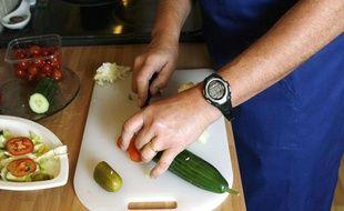 Un homme découpe des légumes.