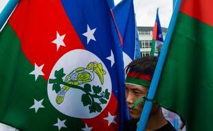 Un homme manifeste, un drapeau Chin à la main, contre le conflit qui secoue sa région, le 13 juillet 2019 à Rangoun.
