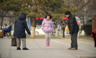 Une petite fille joue à la corde à sauter avec sa famille à Pékin, le 7 décembre 2012