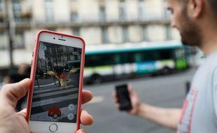Un joueur regarde l'application Pokemon Go sur son smartphone dans les rues de Paris, le 26 juillet 2016