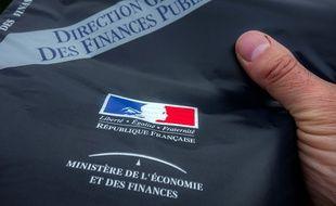 Une personne présentente l'enveloppe contenant la déclaration d'impôts envoyée aux contribuables par le ministère de l'Economie et des Finances, le 10 avril 2014 à Lille