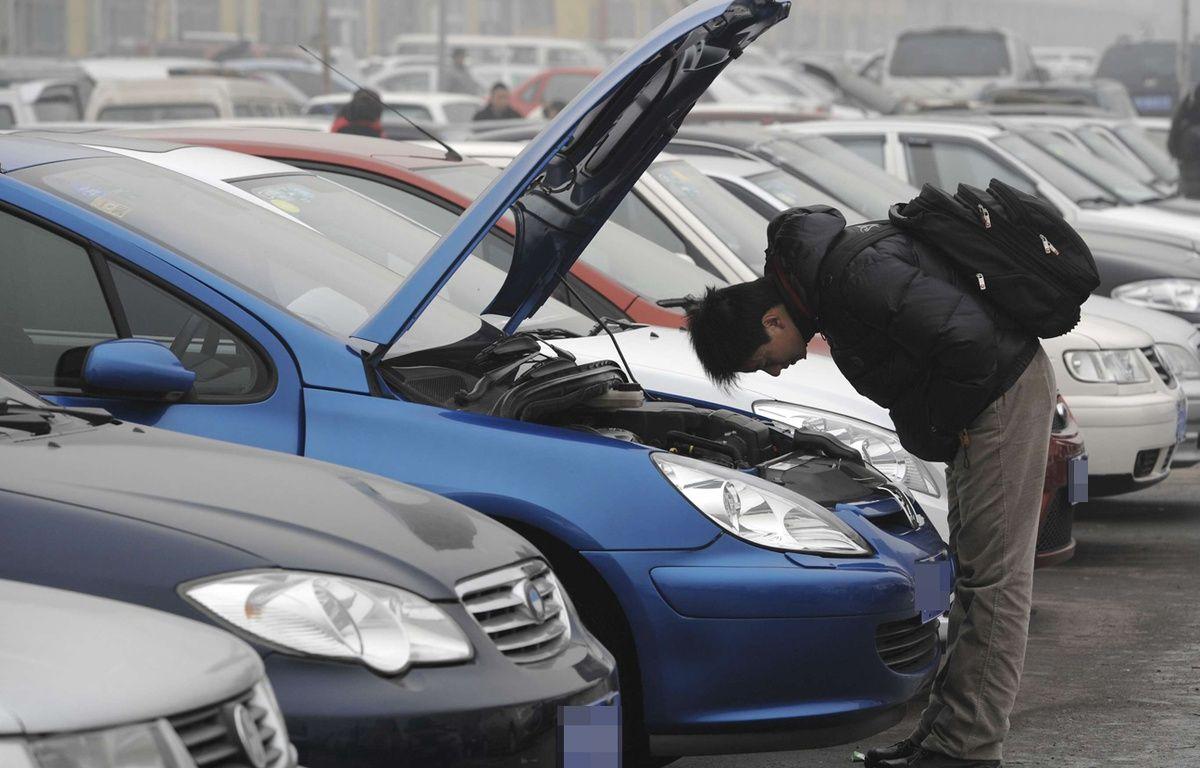 Un homme inspecte une voiture d'occasion (illustration). – Andy Wong/AP/Sipa