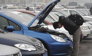 Un homme inspecte une voiture d'occasion (illustration).