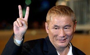 Le réalisateur Takeshi Kitano fait le «V» de la victoire à la Mostra de Venise, le 2 septembre 2003.