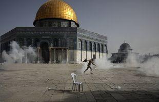 Un Palestinien fuit des gaz lacrymogènes lors d'affrontements avec les forces de sécurité israéliennes devant la mosquée du Dôme du Rocher dans l'enceinte de la mosquée Al Aqsa dans la vieille ville de Jérusalem lundi 10mai 2021.