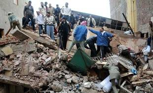 Des hommes cherchent des survivants dans les décombres d'une usine d'Alexandrie (Egypte) qui s'est effondrée le 12 décembre 2010.