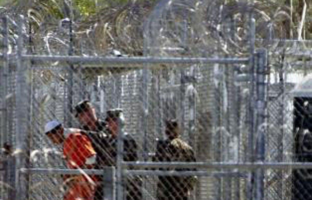 Un détenu de Guantanamo encadré par des soldats américains, en 2002 – Peter Muhly AFP