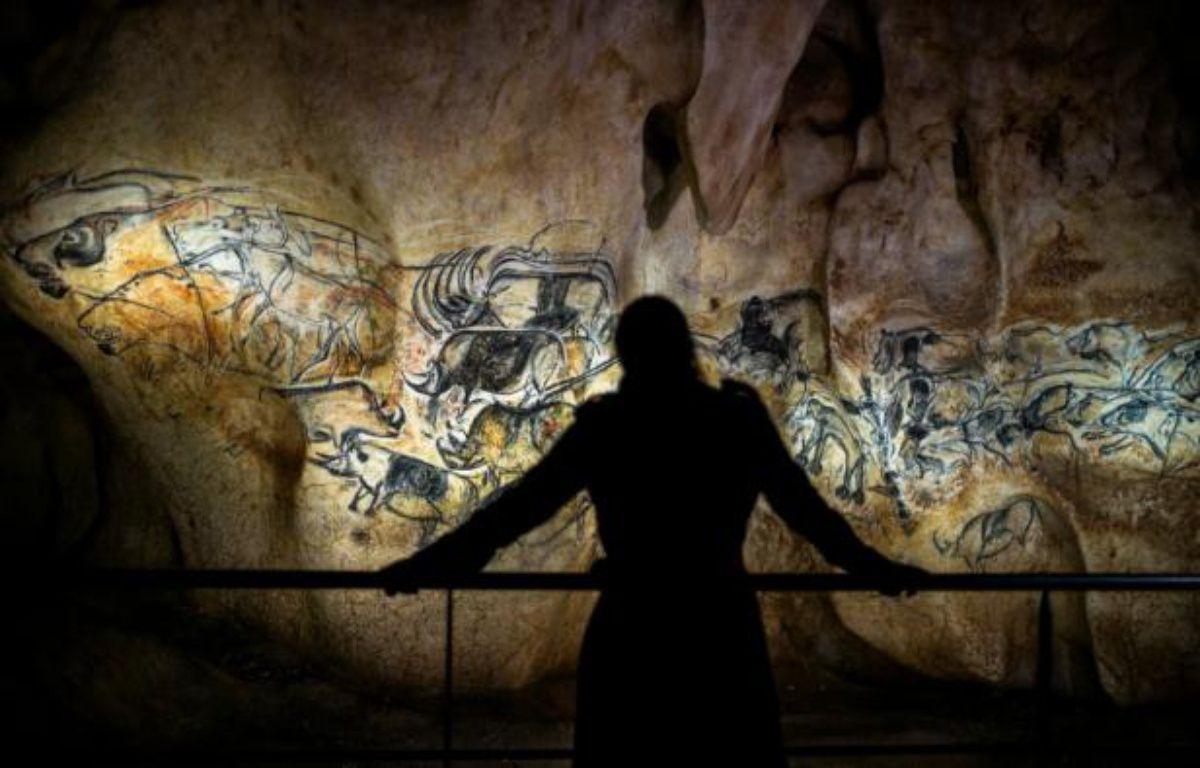 Une personne observe une reproduction à taille réelle des fresques de la grotte Chauvet, à Vallon Pont d'Arc le 8 avril 2015 – JEFF PACHOUD AFP