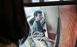A picture taken on May 11, 2011, in Paris shows a woman looking at a still frame taken from a surveillance camera, and released on the Italian RAI TV website, of Xavier Dupont de Ligonnes, a man suspected of murdering his family, withdrawing cash from an ATM in Roquebrune-sur-Argens on April 14. French authorities issued an international arrest warrant on May 10, 2011 for Xavier Dupont de Ligonnes, suspected of murdering his wife and four children before going on the run. AFP PHOTO THOMAS COEX