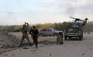 TOPSHOTS Des membres des forces armées libyennes tirent en direction de milices islamistes, le 3 novembre 2014, près du port de Benghazi, dans l'est du pays.