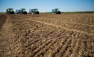 Des engins agricoles se positionnent sur un champ. Photo d'illustration.