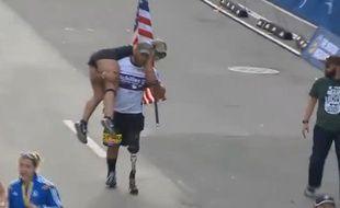 Ce vétéran américain aide une jeune femme à franchir la ligne d'arrivée.