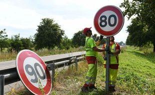 Des hommes changent le panneau de vitesse sur une route départementale.
