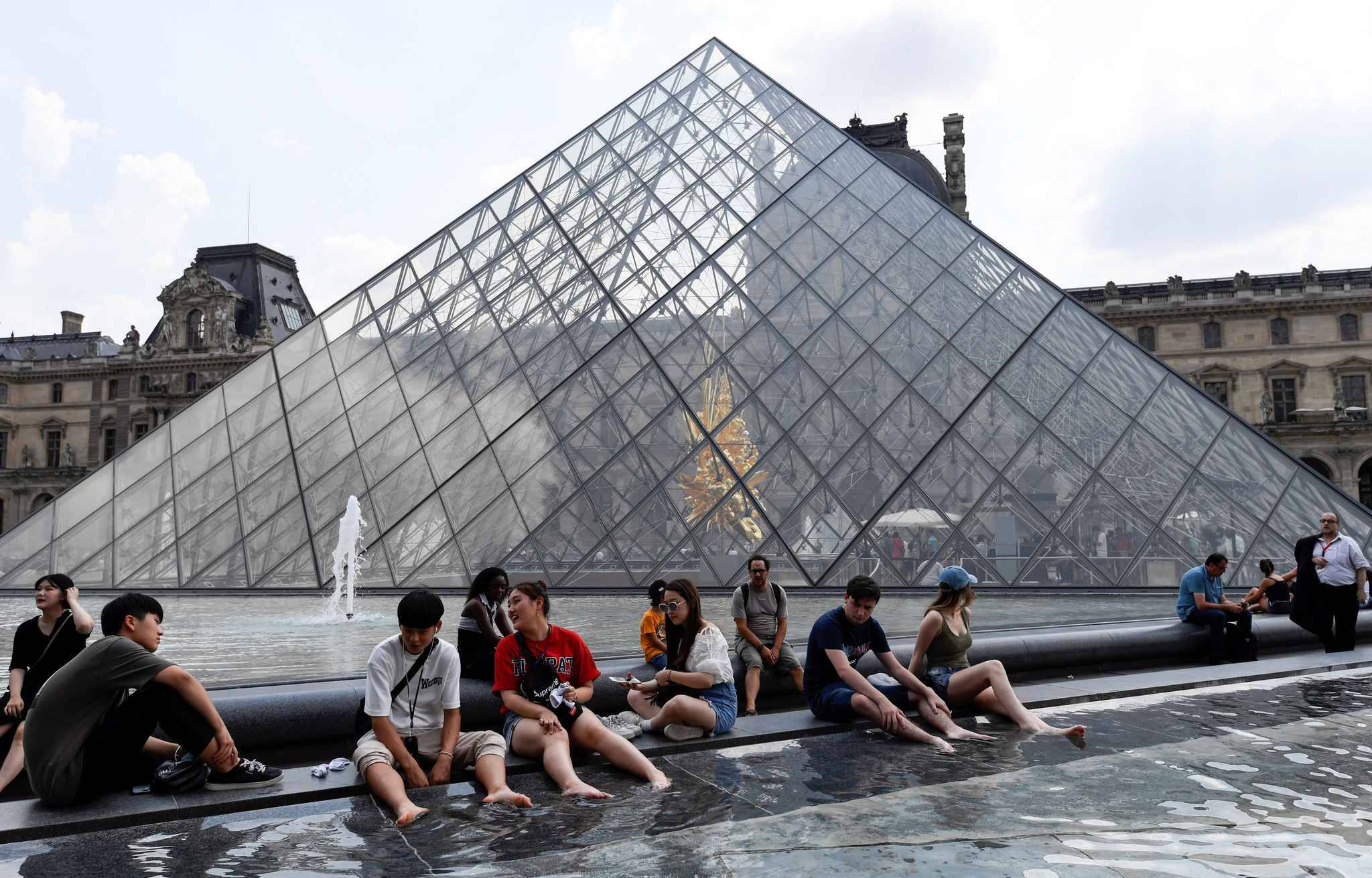 People cool themselves at the fountain of the Louvre Pyramid in Paris on July 25, 2018, as a heatwave continues across northern Europe, with wildfires breaking out in northern Scandanavia and Greece.