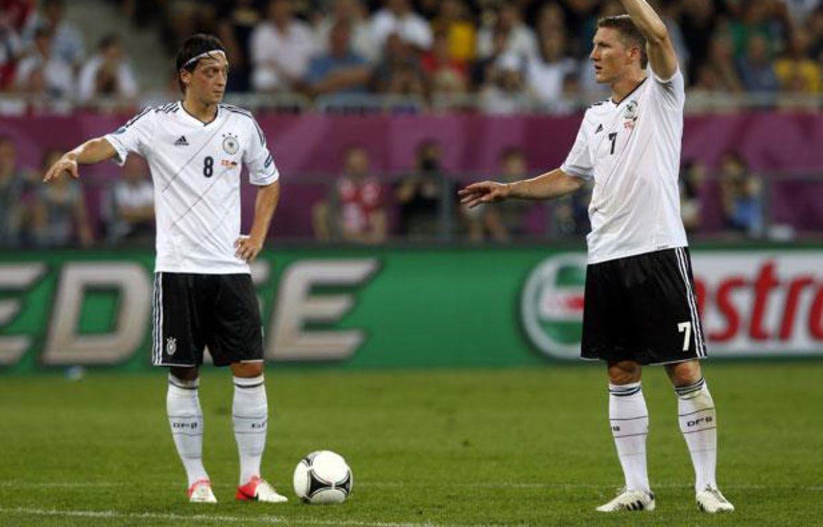 Les joueurs allemands, Mesut Ozil (à g.) et Bastian Schweinsteiger, lors du quart de finale de l'Euro contre la Grèce, le 22 juin 2012. – REUTERS