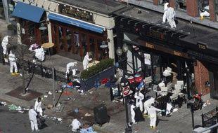 Des enquêteurs examinent la scène du double attentat de Boston qui a fait 3 morts et 176 blessés le 15 avril 2013.