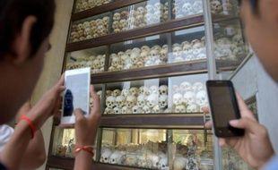 Des visiteurs prennent en photo des crânes des victimes des Khmers rouges au mémorial de Choeung Ek à Phnom Penh, le 17 avril 2016