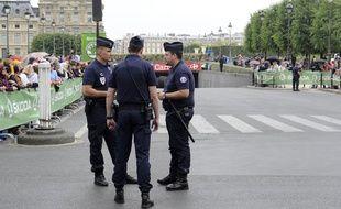 Des policiers montent la garde  près de la Place de la Concorde à Paris avant le départ de la ernière étape du Tour de France, le 26 juillet 2015.