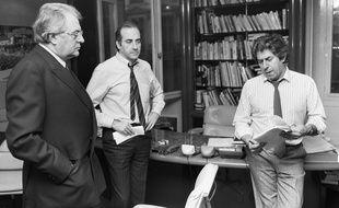 Les journalistes et chroniqueurs Philippe Gildas (D) et Jean-Pierre Elkabbach (C) discutent avec le Premier ministre Pierre Mauroy (G) avant de l'interviewer au journal matinal d'Europe 1, le 27 mars 1984 à Paris.