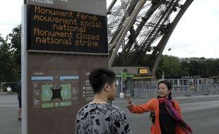 Des touristes le 14 juin 2016 à Paris, devant la Tour Eiffel, fermée pour cause de grève.AP Photo/Bertrand Combaldieu