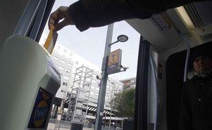 Un usager du tramway toulousain à la station des Arènes.
