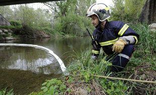 Un pompier surveille un barrage flottant installé sur la rivière le Largue à Saint-Maime, le 02 mai 2010 après une fuite d'hydrocarbure dans une entreprise.