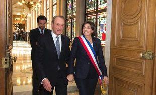 La nouvelle maire de Paris Anne Hidalgo portant son écharpe tricolore, escorte son prédécesseur socialiste Bertrand Delanoë qui quitte l'hôtel de ville après la session inaugurale du conseil de Paris, le 5 avril 2014