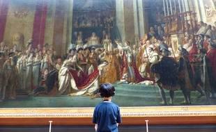 """Un enfant admire """"Le sacre de Napoléon Ier"""" par David, exposé au musée du Louvre. Le 13 juillet 2018."""
