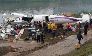 Des équipes de secours autour du fuselage de l'ATR 72-600 de la TransAsia sorti de l'eau, le 5 février 2015 à Taipei