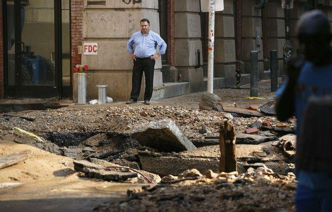 Un homme se tient près de l'endroit où une des canalisations principales de la ville de Philadelphie s'est produite tôt le mardi 3 juillet 2018. Un certain nombre de rues du centre-ville ont été fermées.