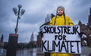 Greta Thunberg, 16 ans, tient une pancarte