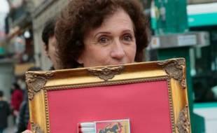 Une femme porte un cadre avec une boite d'allumettes contenant des tampons hygiéniques, le 11 novembre 2015 à Paris